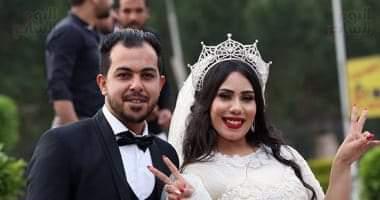 صورة عروسان يحتفلان بزفافهما بحضور اسري في احدي الحدائق العامه بمنطقه الدقي قبل موعدالحظر